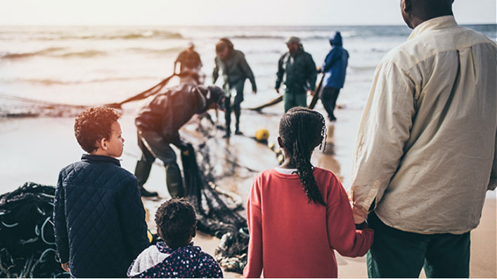 A father and his three children looking at the sea as fishermen gather a net