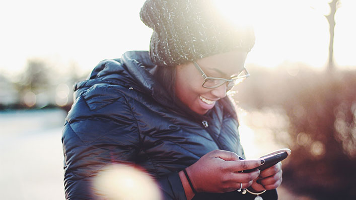 A Black woman looking at her cell phone and smiling