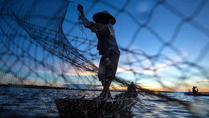 A fishermen casting his nest at sea