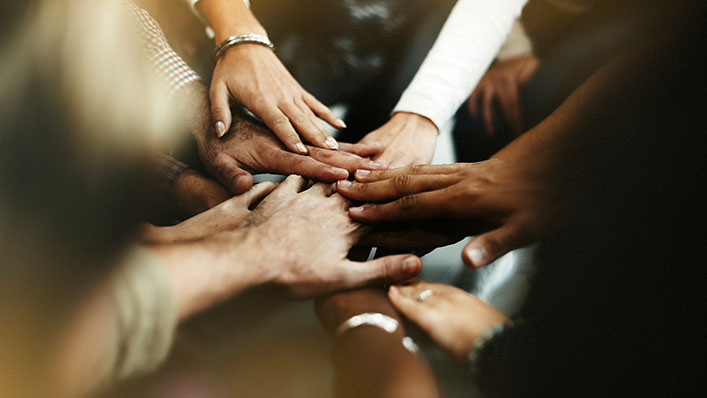 A group of diverse peoples' hands stacking on top of each other