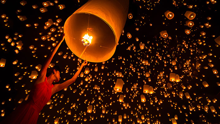 A night sky full of beautiful floating paper lanterns illuminated by flames