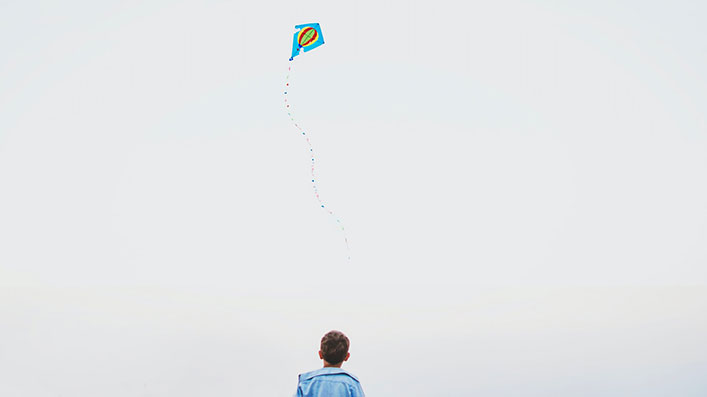 A boy flying a kite alone