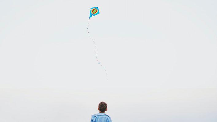 A boy flying a kite alone
