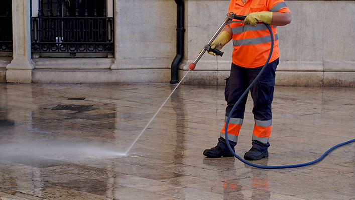 A public worker cleaning the street with a water hose