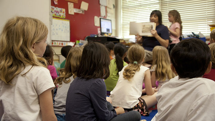 A teacher showing a book to a group of children in a kindergarten classroom