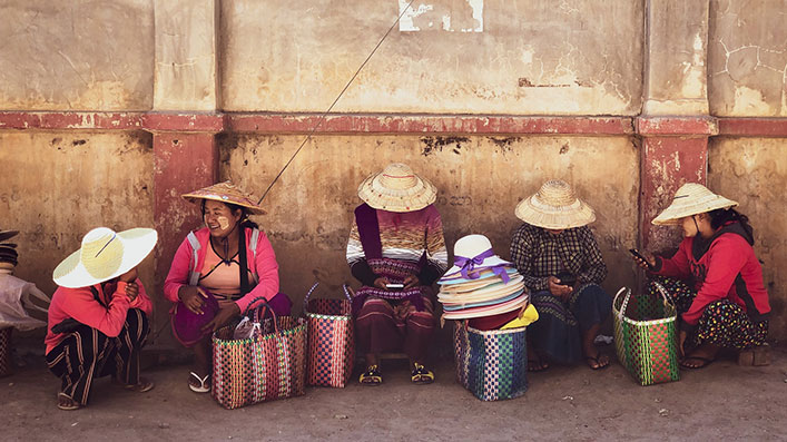 A group of women sitting by concrete wall, selling items in baskets