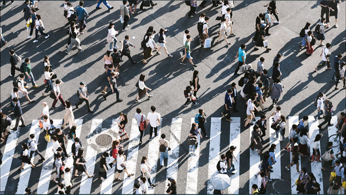 Many people walking in separate directoins across a zebra line on a busy street
