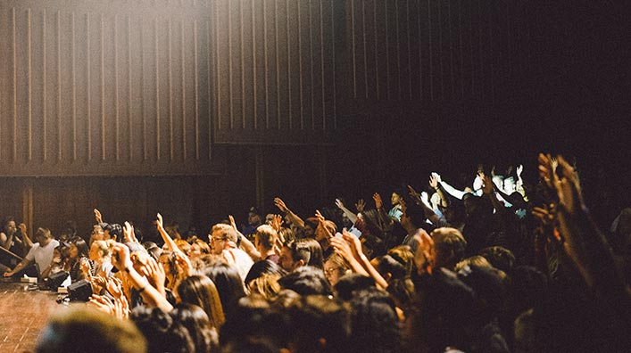 A group of people raising their hands on an auditorium