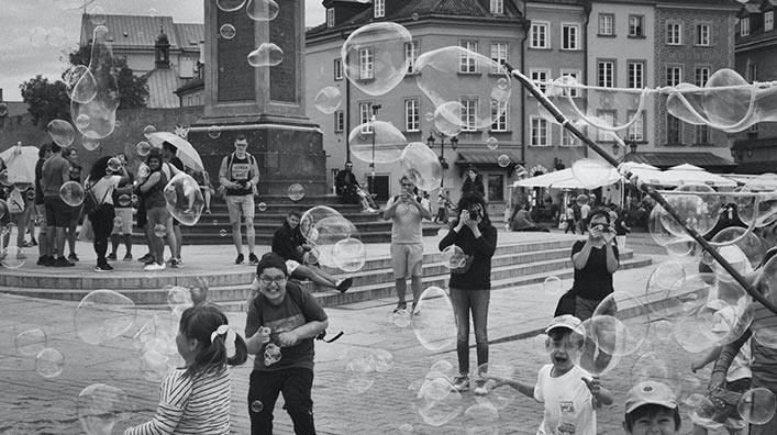 A group of children having fun and playing with soap bubbles in an open square.